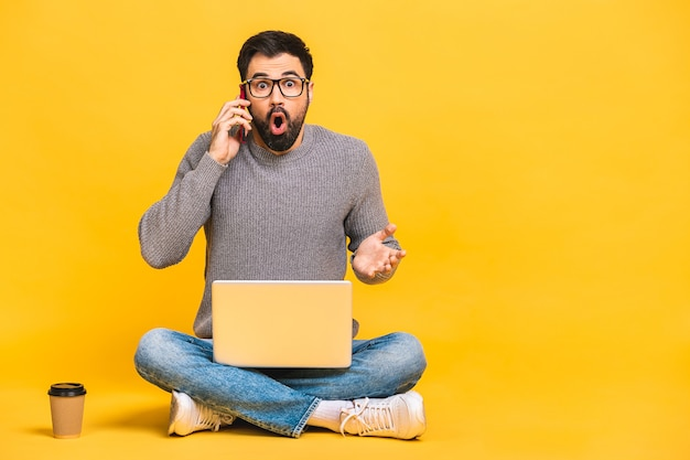Young bearded man sitting on the floor with laptop and talking at phone. isolated over yellow background.