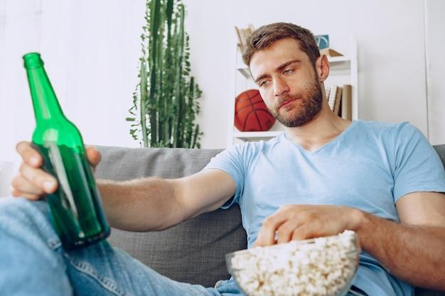 映画を見ながら、ビールとポップコーンと一緒にソファに座っている若いひげを生やした男