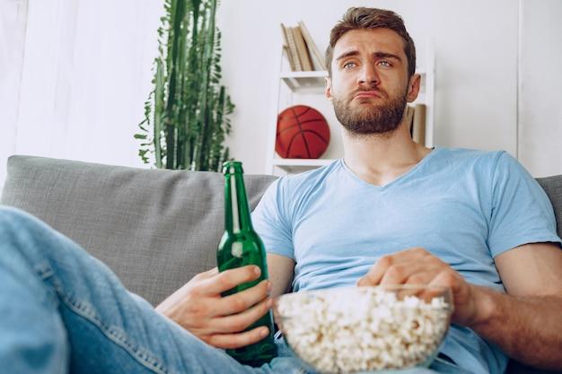 映画を見ながらビールとポップコーンと一緒にソファに座っている若いひげを生やした男