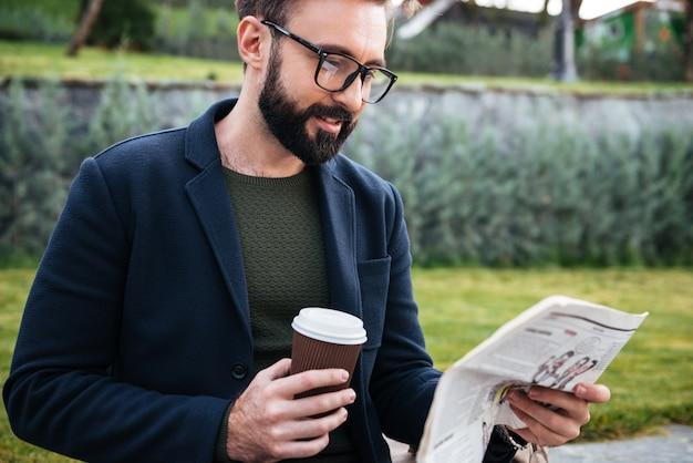 Молодой бородатый человек сидит на улице читает газету