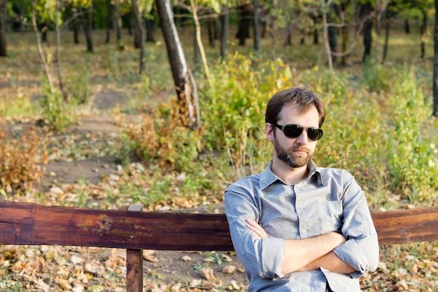 Молодой бородатый мужчина сидит со скрещенными руками на деревенской деревянной скамье, глубоко задумавшись