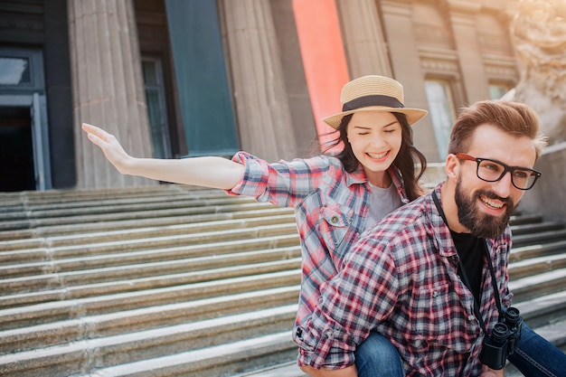 Young and bearded man smiles and hold girlfriend on back. she keeps hands aside of body. woman looks down. she is happy.