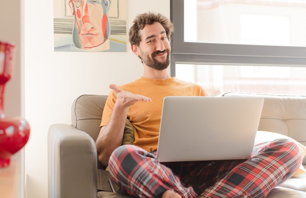 Young bearded man smiling cheerfully feeling happy and showing a concept in copy space with palm of hand and sitting with a laptop
