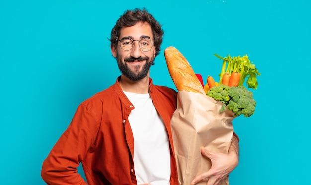 턱수염을 기른 젊은 남자는 손을 엉덩이에 대고 행복하게 웃고 자신감 있고 긍정적이고 자랑스럽고 친근한 태도로 야채 가방을 들고 있다