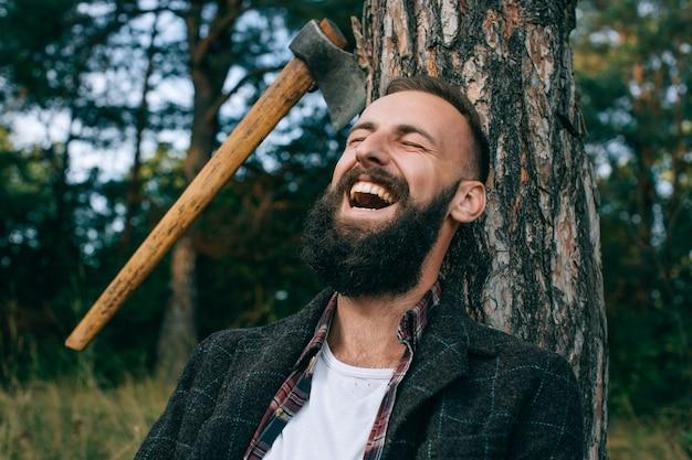Молодой бородатый мужчина широко улыбается в лесу на открытом воздухе. счастливый человек