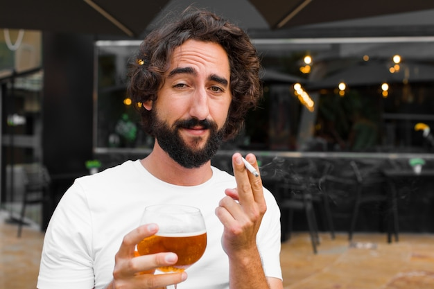 Young bearded man smoking and drinking a beer