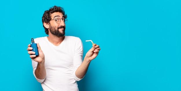 Молодой бородатый мужчина курит с вейпером