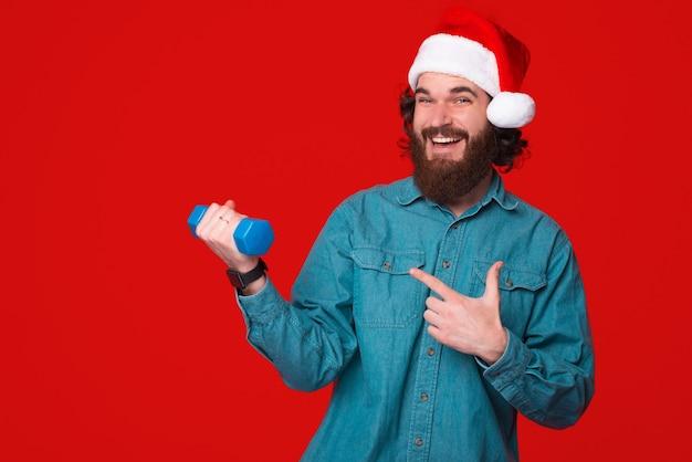 젊은 수염 난 남자는 크리스마스 모자를 쓰고 아령을 가리키는 동안 체육관에 갈 것을 제안합니다.