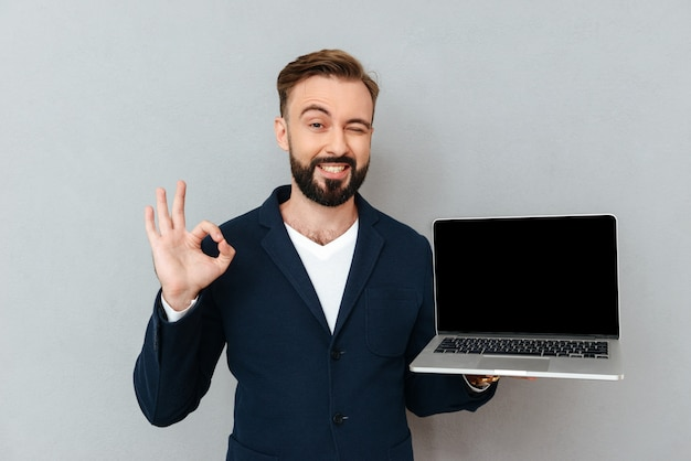 Young bearded man in suit looking camera while holding laptop computer isolated