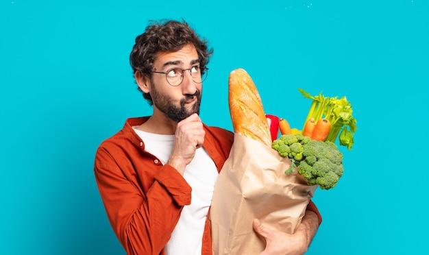 젊은 수염을 기른 남자가 생각하고 의심스럽고 혼란스러워하며 다른 옵션으로 어떤 결정을 내리고 야채 가방을 들고 있는지 궁금해합니다.