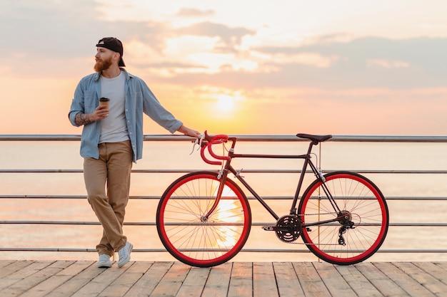 Giovane uomo barbuto che viaggia in bicicletta al tramonto sul mare