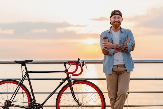 Young bearded man traveling on bicycle at sunset sea