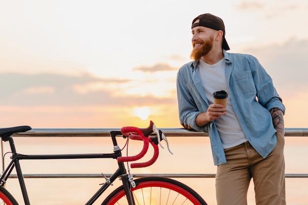 夕焼けの海で自転車で旅行する若いひげを生やした男