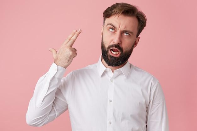 若いひげを生やした男は、ピンクの背景の上に分離された2本の指でヘッドショットで自殺しようとします。