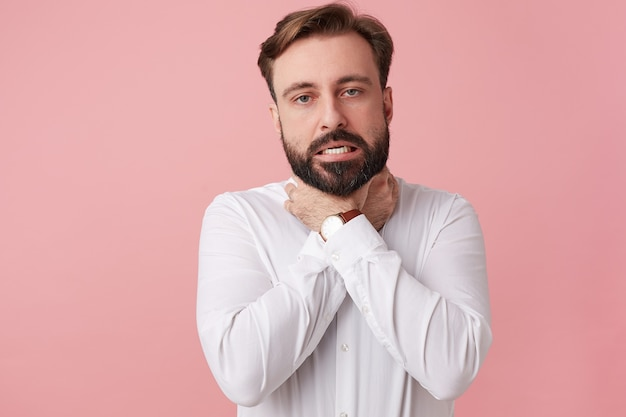 Young bearded man try kill himself, strangling himself with both hands and choking isolated over pink background.