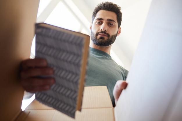 Молодой бородатый мужчина распаковывает книги из коробки во время переезда в новый дом