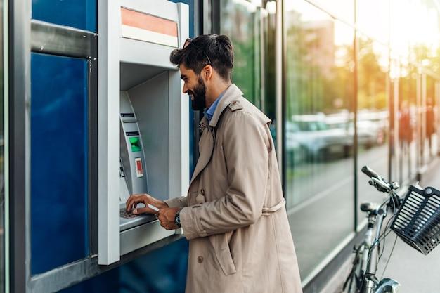 Молодой бородатый мужчина с помощью банкомата для снятия денег.