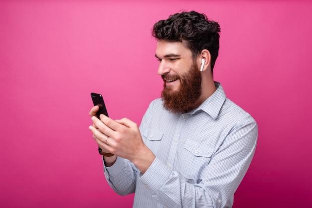 분홍색 배경에 전화기와 이어폰을 사용하는 수염난 청년. 무선 기술.