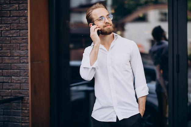 Молодой бородатый мужчина с помощью телефона и прогулки по улице