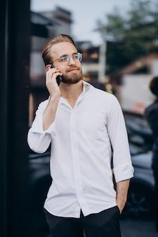電話を使用して通りを歩いている若いひげを生やした男