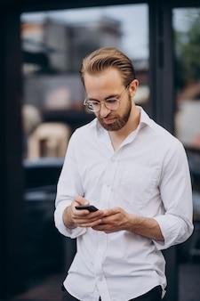 Giovane uomo barbuto che usa il telefono e cammina per strada