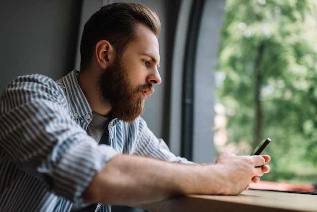 Young bearded man using smartphone, communication, shopping online, sitting at home