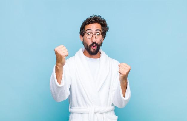 勝者のように信じられないほどの成功を祝うバスローブを着た若いひげを生やした男は、興奮して幸せそうに見えます。