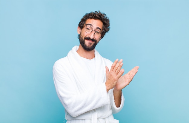 Молодой бородатый мужчина в купальном халате чувствует себя счастливым и успешным, улыбается и хлопает в ладоши, произнося поздравления аплодисментами
