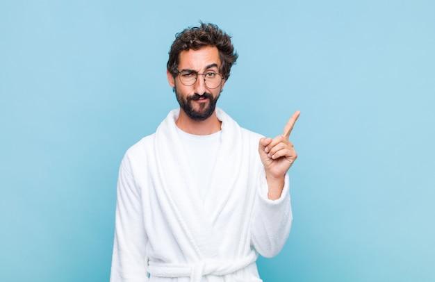 素晴らしいアイデアを実現した後、天才が誇らしげに指を空中に持ち上げているようなバスローブを着た若いひげを生やした男は、ユーレカと言った