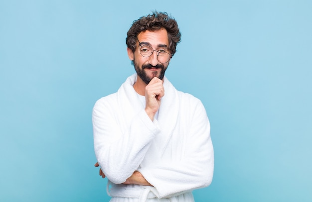 Молодой бородатый мужчина в купальном халате выглядит счастливым и улыбается, положив руку на подбородок, задает вопрос или задает вопрос, сравнивая варианты