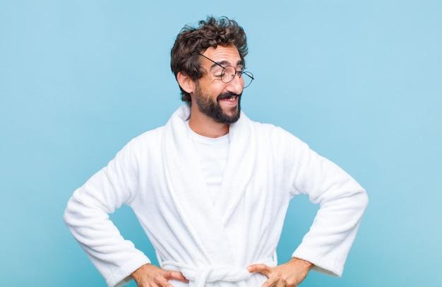 Молодой бородатый мужчина в купальном халате выглядит счастливым, веселым и уверенным, гордо улыбается и смотрит в сторону, положив руки на бедра