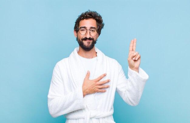 Молодой бородатый мужчина в купальном халате выглядит счастливым, уверенным и заслуживающим доверия, улыбается и показывает знак победы, с позитивным настроем