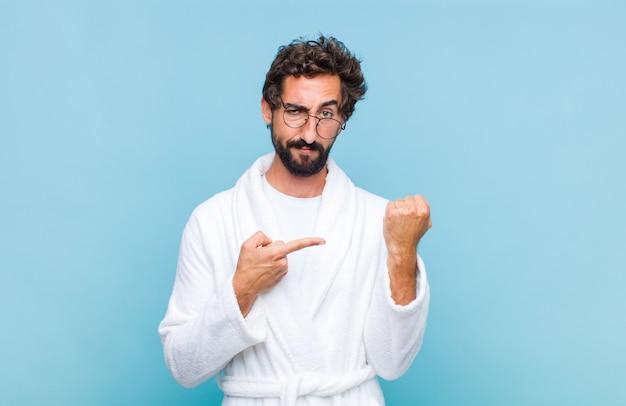 せっかちで怒っているように見えるバスローブを着て、時計を指差して、時間厳守を求めて、時間通りになりたい若いひげを生やした男