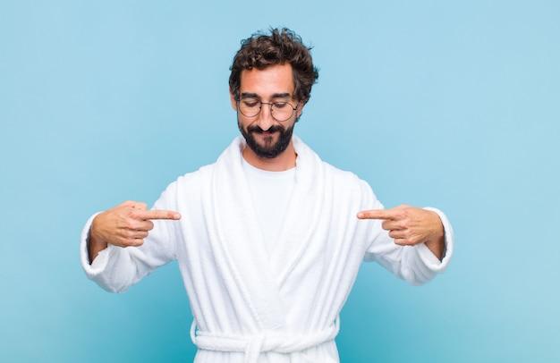 Молодой бородатый мужчина в купальном халате выглядит гордым, позитивным и непринужденным, указывая на грудь обеими руками