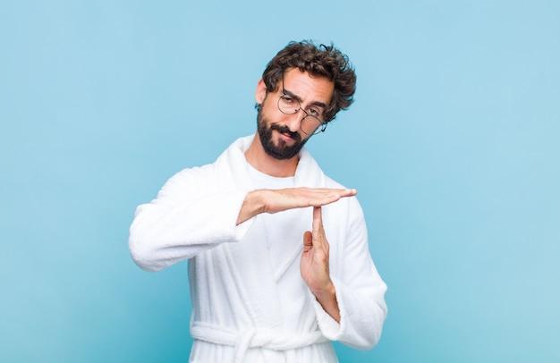 真面目で、厳しく、怒って、不機嫌そうに見えるバスローブを着た若いひげを生やした男は、タイムアウトの兆候を作ります