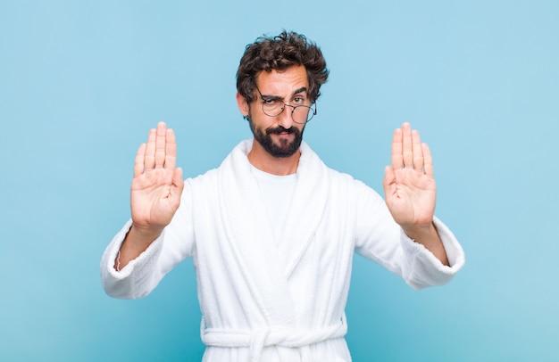 真面目で不幸、怒り、不機嫌そうなバスローブを着た若いひげを生やした男性は、立ち入りを禁止したり、両手のひらを開いて停止すると言ったりします