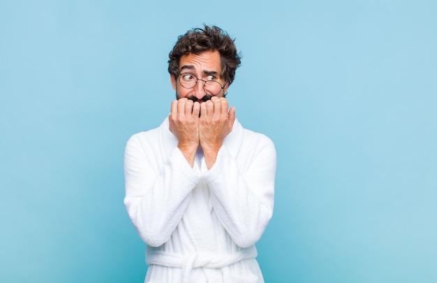 Молодой бородатый мужчина в купальном халате выглядит обеспокоенным, встревоженным, напряженным и напуганным, кусает ногти и смотрит в пространство для боковой копии