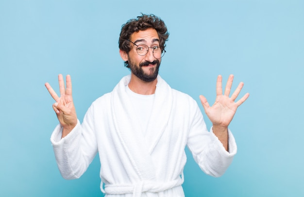 笑顔でフレンドリーに見えるバスローブを着た若いひげを生やした男は、手を前に向けて8番または8番を示し、カウントダウン