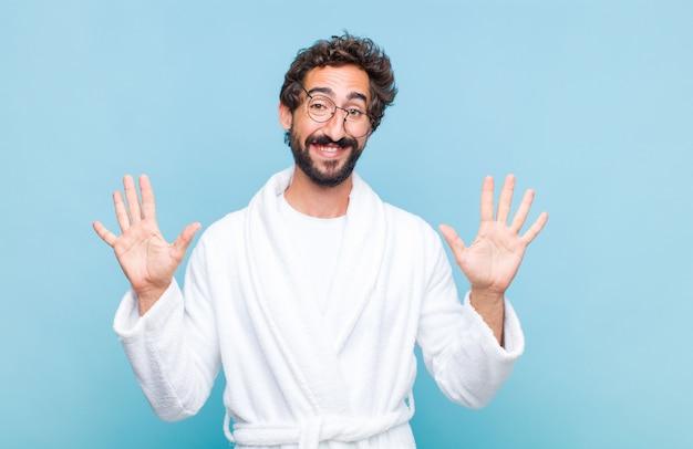 笑顔でフレンドリーに見えるバスローブを着た若いひげを生やした男は、前に手を前に数10または10を示し、カウントダウン