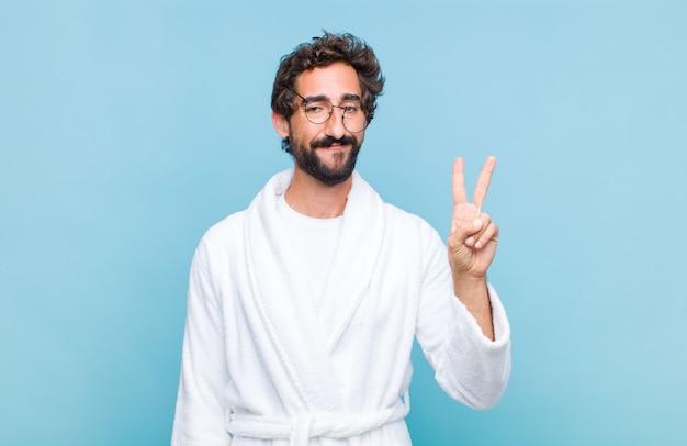 Молодой бородатый мужчина в купальном халате улыбается и выглядит дружелюбно, показывает номер два или секунду рукой вперед и ведет обратный отсчет