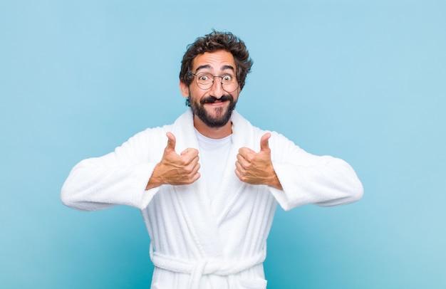 両方の親指を立てて、幸せで、前向きで、自信を持って、成功しているように広く笑っているバスローブを着た若いひげを生やした男
