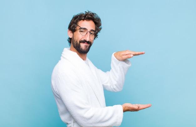笑顔、幸せ、前向き、満足感、コピースペースでオブジェクトやコンセプトを保持または表示するバスローブを着て若いひげを生やした男