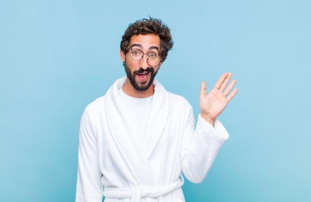 Молодой бородатый мужчина в купальном халате счастливо и весело улыбается, машет рукой, приветствует и приветствует вас или прощается