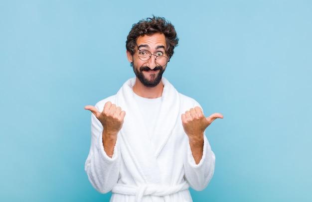 Молодой бородатый мужчина в купальном халате радостно улыбается и выглядит счастливым, чувствуя себя беззаботным и позитивным, подняв оба пальца вверх