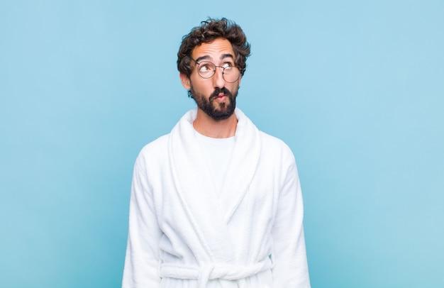 心配して、混乱して、無知な表情でバスローブを着て、コピースペースを見上げて、疑っている若いひげを生やした男