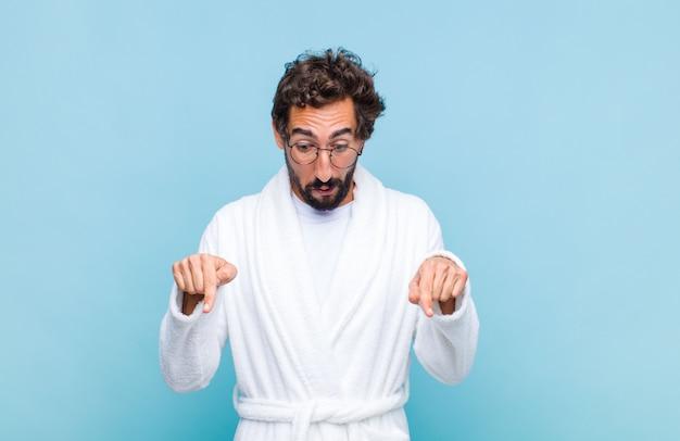 Молодой бородатый мужчина в купальном халате с открытым ртом, направленным вниз обеими руками