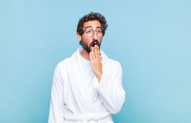 Молодой бородатый мужчина в халате лениво зевает рано утром