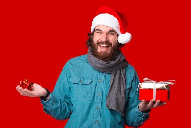 Молодой бородатый мужчина в шляпе рождества держит в руках большой и маленький подарок.