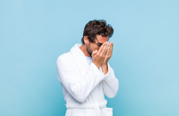 Young bearded man wearing a bath robe covering eyes with hands with a sad, frustrated look of despair, crying, side view