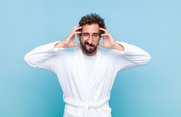 Young bearded man wearing a bath robe feeling frustrated and annoyed, sick and tired of failure, fed-up with dull, boring tasks